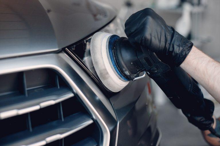 Man in a garage. Worker polish a car.